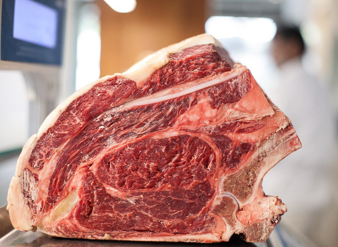 A large cut of meat with distinct bones and marbling sits on a butcher counter