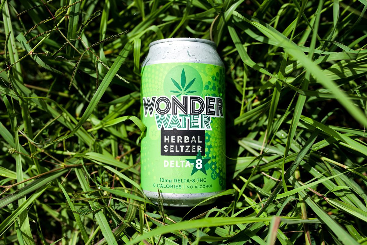 a green can of selter spiked with delta-8. the can is resting on a bed of grass