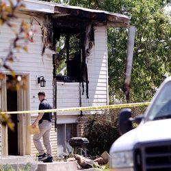 An official walks into a burned out home in West Valley City on Monday, June 5, 2017. A woman was found dead following the early morning blaze.
