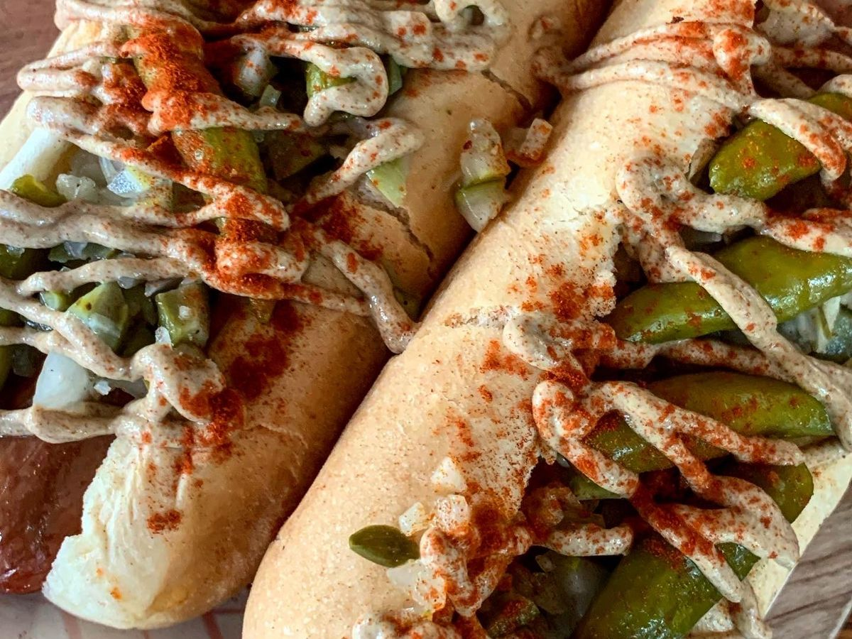 A close-up on two fully loaded and sauce-drizzled hotdogs
