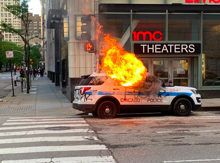 A Chicago police SUV burns outside AMC Theaters Saturday during clashes between protesters and police in River North.