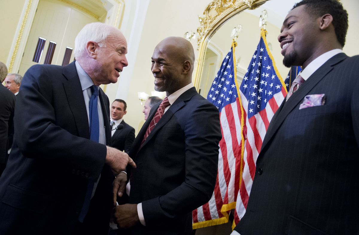 Senator John McCain meeting with former heavyweight boxing champion Evander Holyfield and then UFC light heavyweight champion Jon Jones at an event focused on head injury prevention in 2015.