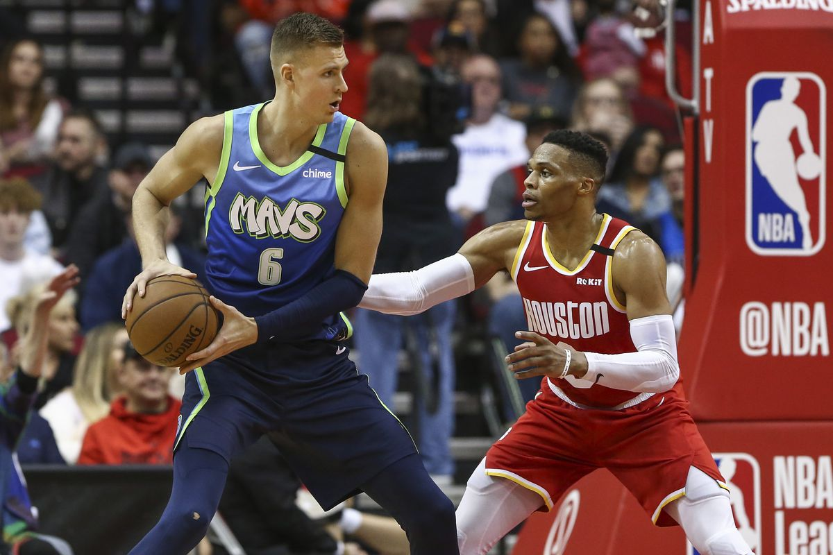 Dallas Mavericks forward Kristaps Porzingis controls the ball as Houston Rockets guard Russell Westbrook defends during the fourth quarter at Toyota Center.