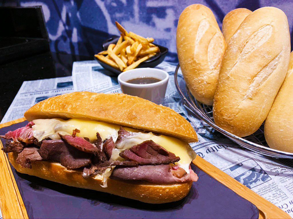 A French dip with fries in the background and French rolls in a basket to the left