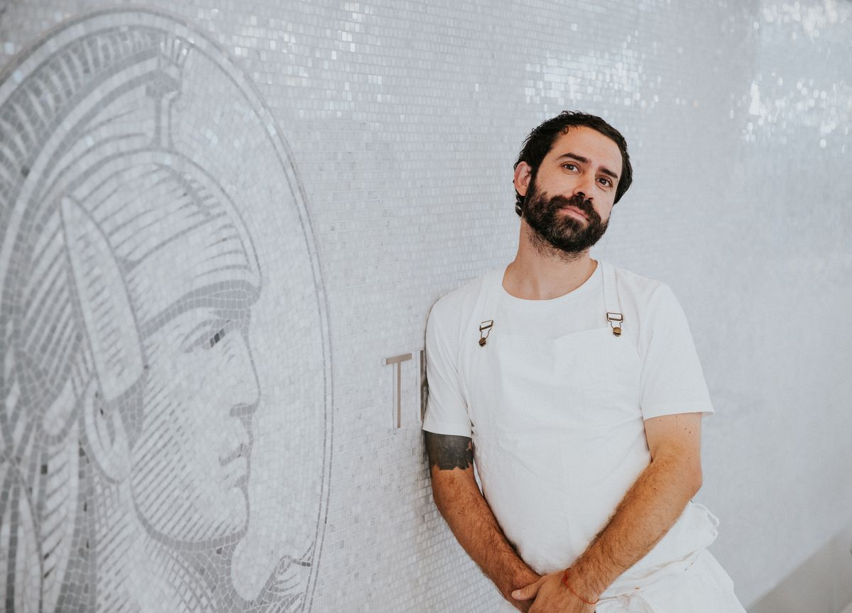 A man in a white chef's apron leans against a white tile wall