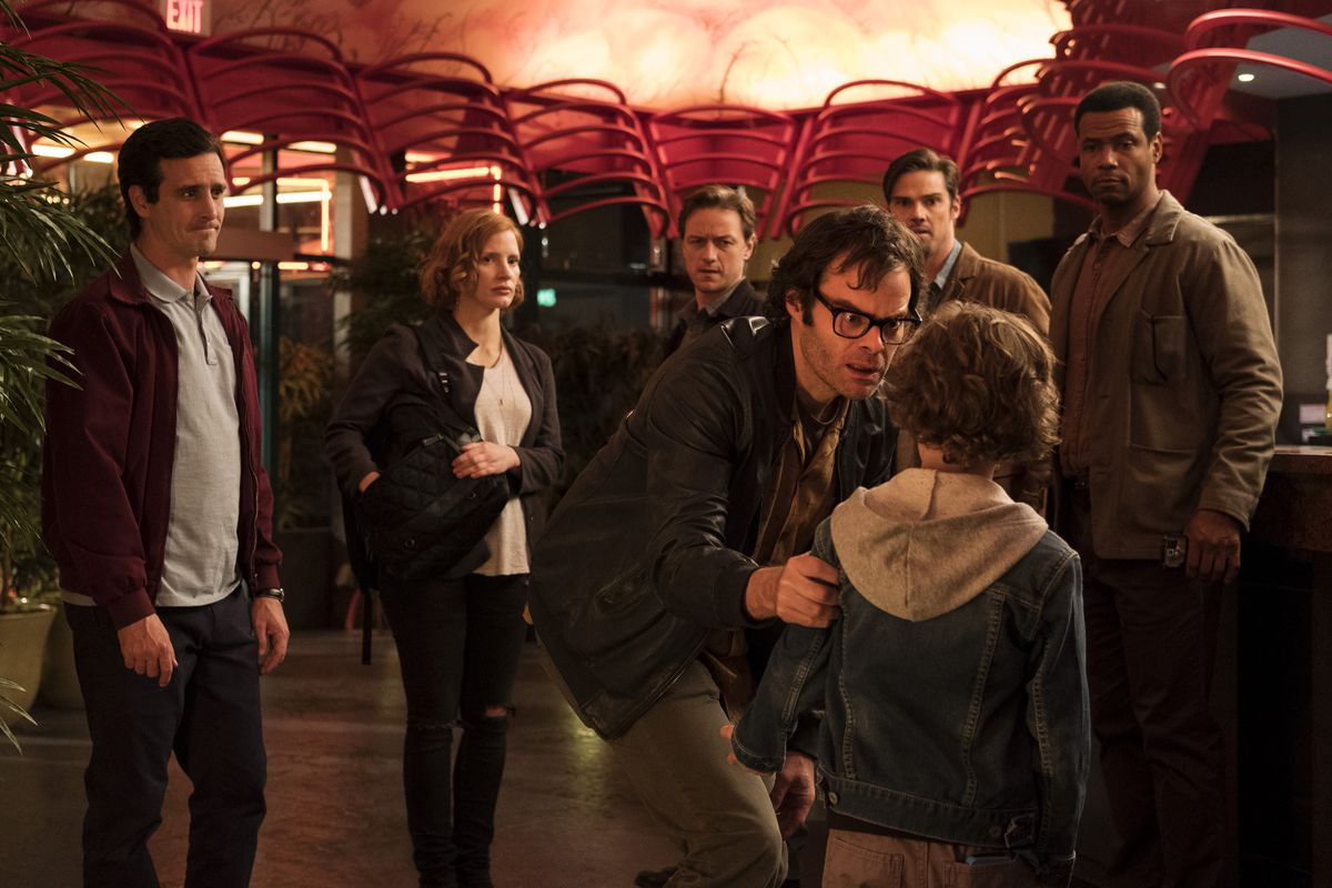 Richie (Hader) confronts a young boy as Eddie (Ransone) and the other Losers look on.