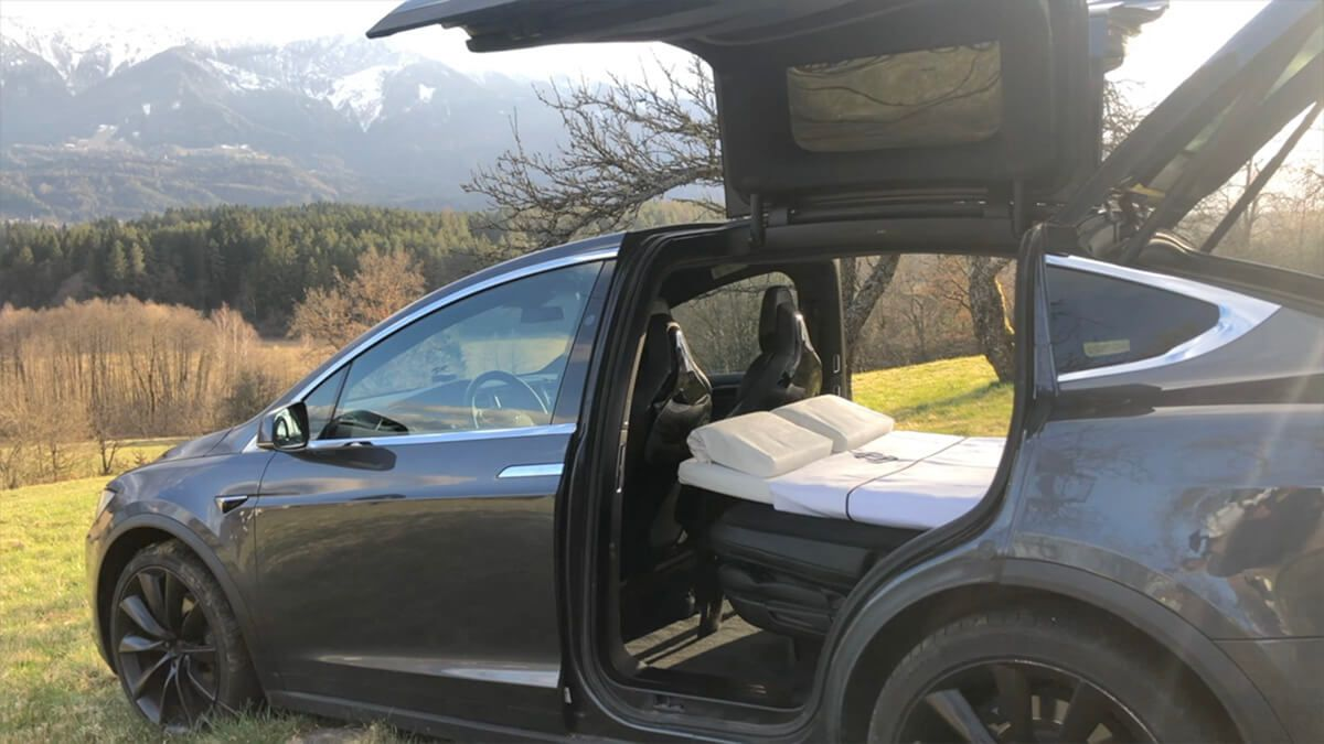 A Tesla Model X has its wing doors open and inside there is a white bed with two pillows. The car sits in a field in a mountainous region.