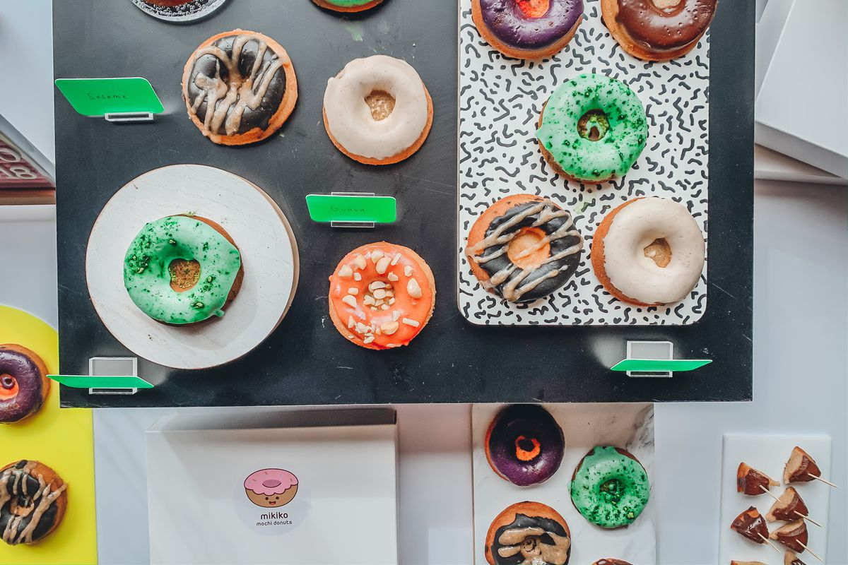 Several Mikiko doughnuts sit on black tables with boxes nearby