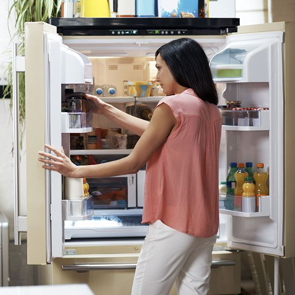 Person checking food in fridge.