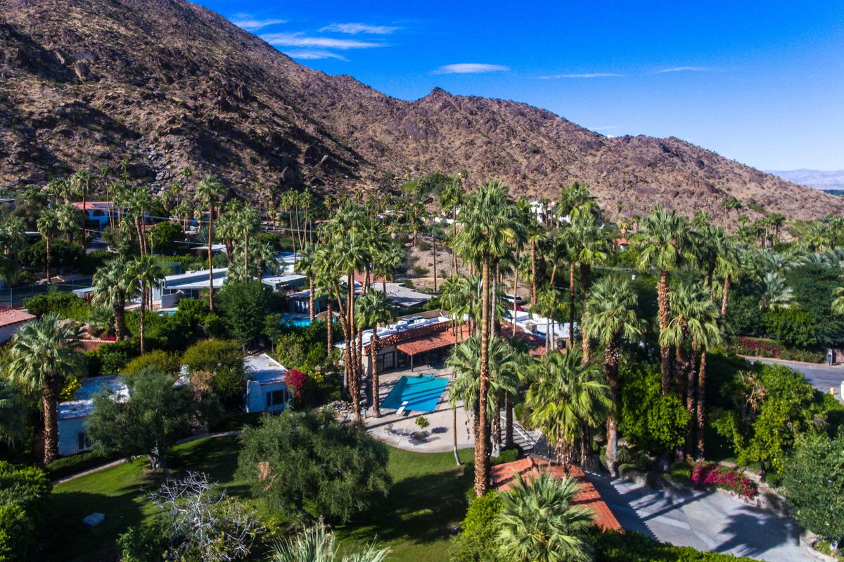 Aerial shot of property nestled against a mountain with pool and surrounding palm trees.