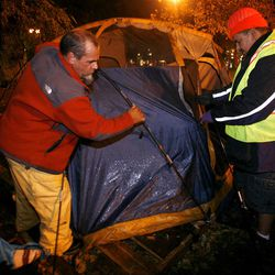 Occupy Salt Lake protestors Ron Hardy, left, and Roy Begay break down a tent before vacating Pioneer Park in Salt Lake City on Saturday, Nov. 12, 2011.
