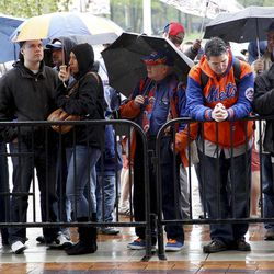 Fans stand in the rain while looking through the gates into Citi Field after the baseball game between the New York Mets and San Francisco Giants was postponed due to weather, Sunday, April 22, 2012, in New York.