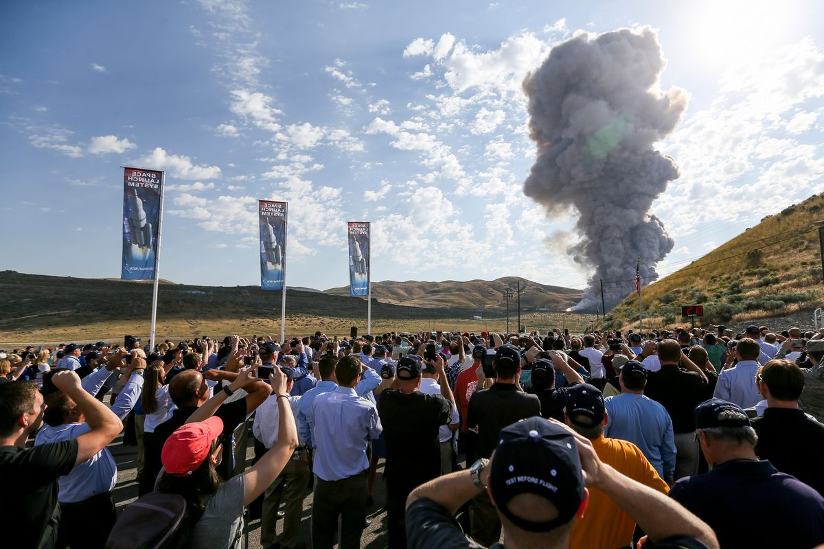 People watch a ground test of the five-segment rocket motor that will be used for NASA's heavy-lift Space Launch System at the Orbital ATK facility in Promontory on Tuesday, June 28, 2016.
