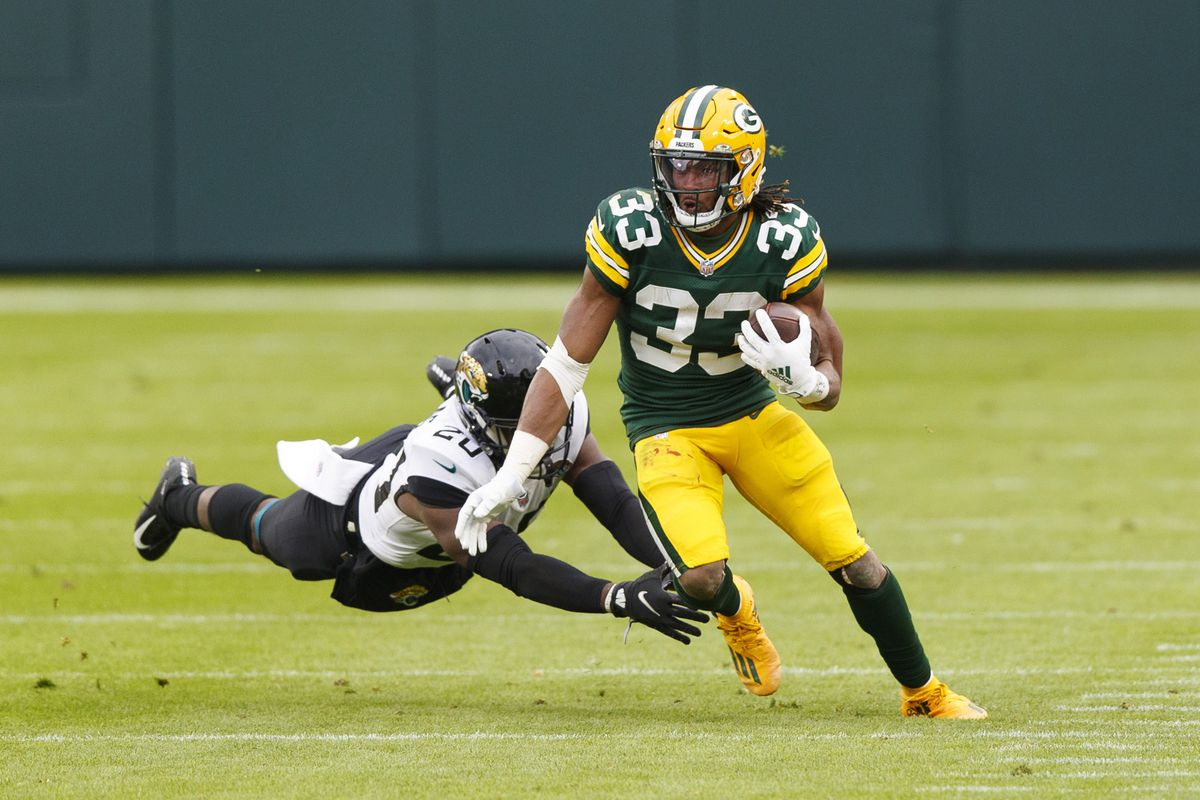 Green Bay Packers running back Aaron Jones (33) runs the football against Jacksonville Jaguars safety Daniel Thomas (20) during the fourth quarter at Lambeau Field.