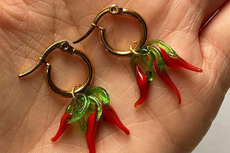 A set of hoop earrings with glass red peppers hanging from the hoops