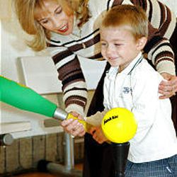 Marci Katzenbach helps her son, Zachary, swing as part of the training exercises. The program is designed for children ages 3-7.