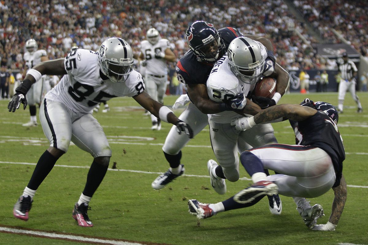 HOUSTON, TX - OCTOBER 09: Running back Darren McFadden #20 of the Oakland Raiders is gang tackled by the Houston Texans on October 9, 2011 at Reliant Stadium in Houston, Texas. Raiders won 25 to 20.(Photo by Thomas B. Shea/Getty Images)