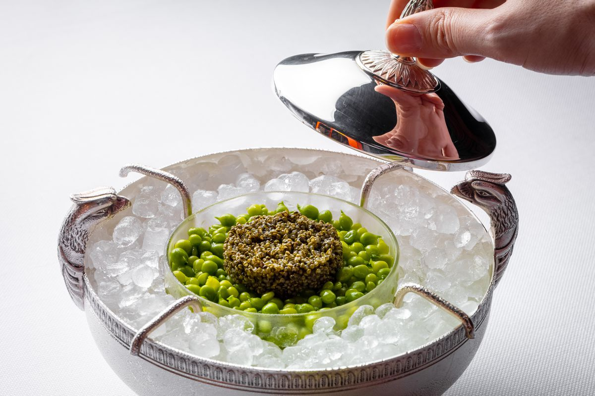 A server decloches the vegan caviar service, which sits in a glass vessel in a steel ice container.