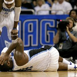 Orlando Magic's Quentin Richardson, left, looks down at injured teammate Glen Davis during the first half of an NBA basketball game against the Charlotte Bobcats, Wednesday, April 25, 2012, in Orlando, Fla.