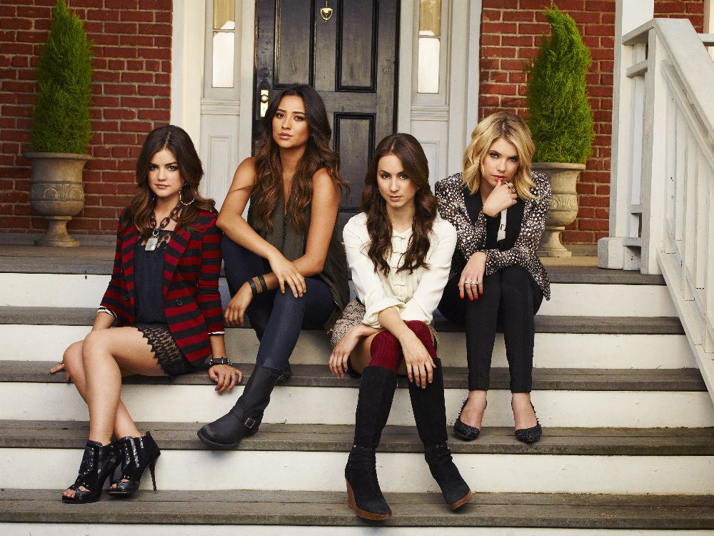 The four main characters of Pretty Little LIars sit on steps in front of a brick house.