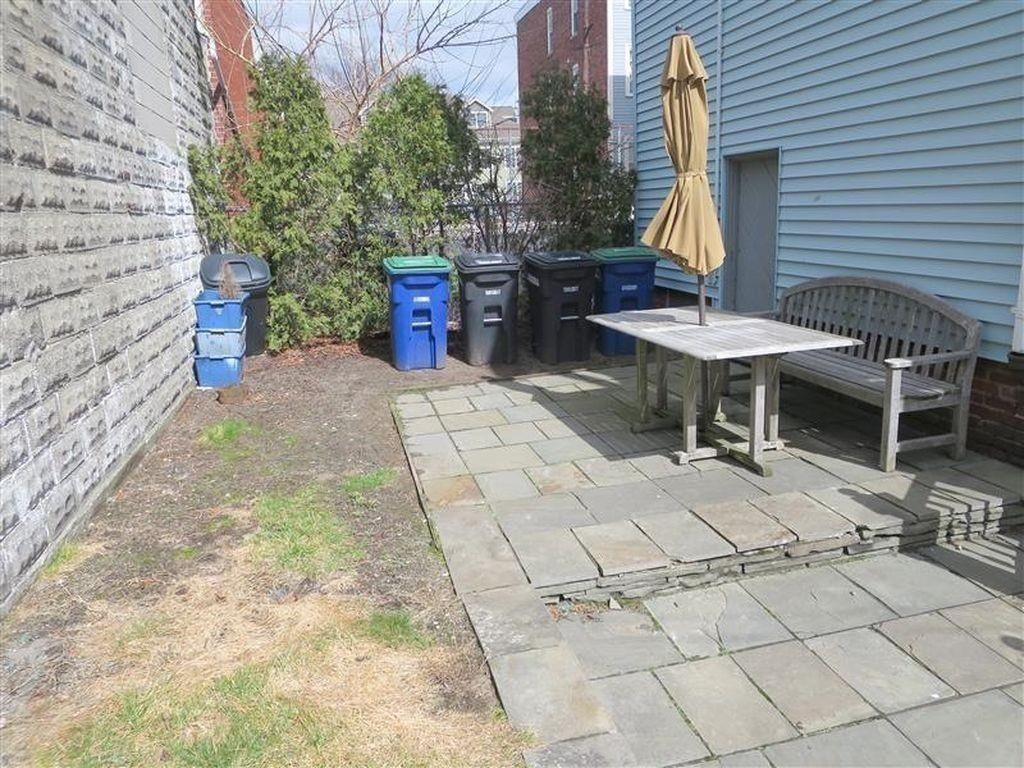 A small patio next to a two-family house, with a table and chairs; and there are recycling carts behind the table.
