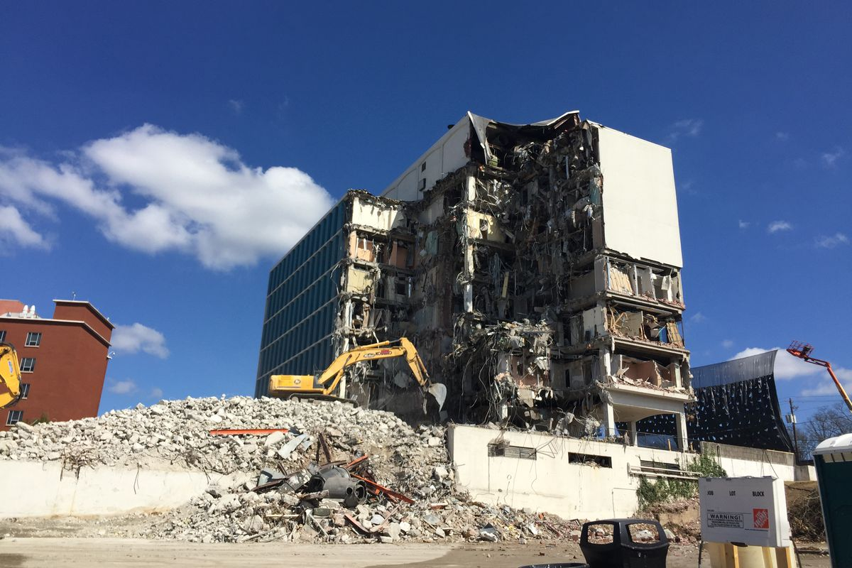 An excavator tears through a seven-story mid-century building, with part of the tower already demolished.