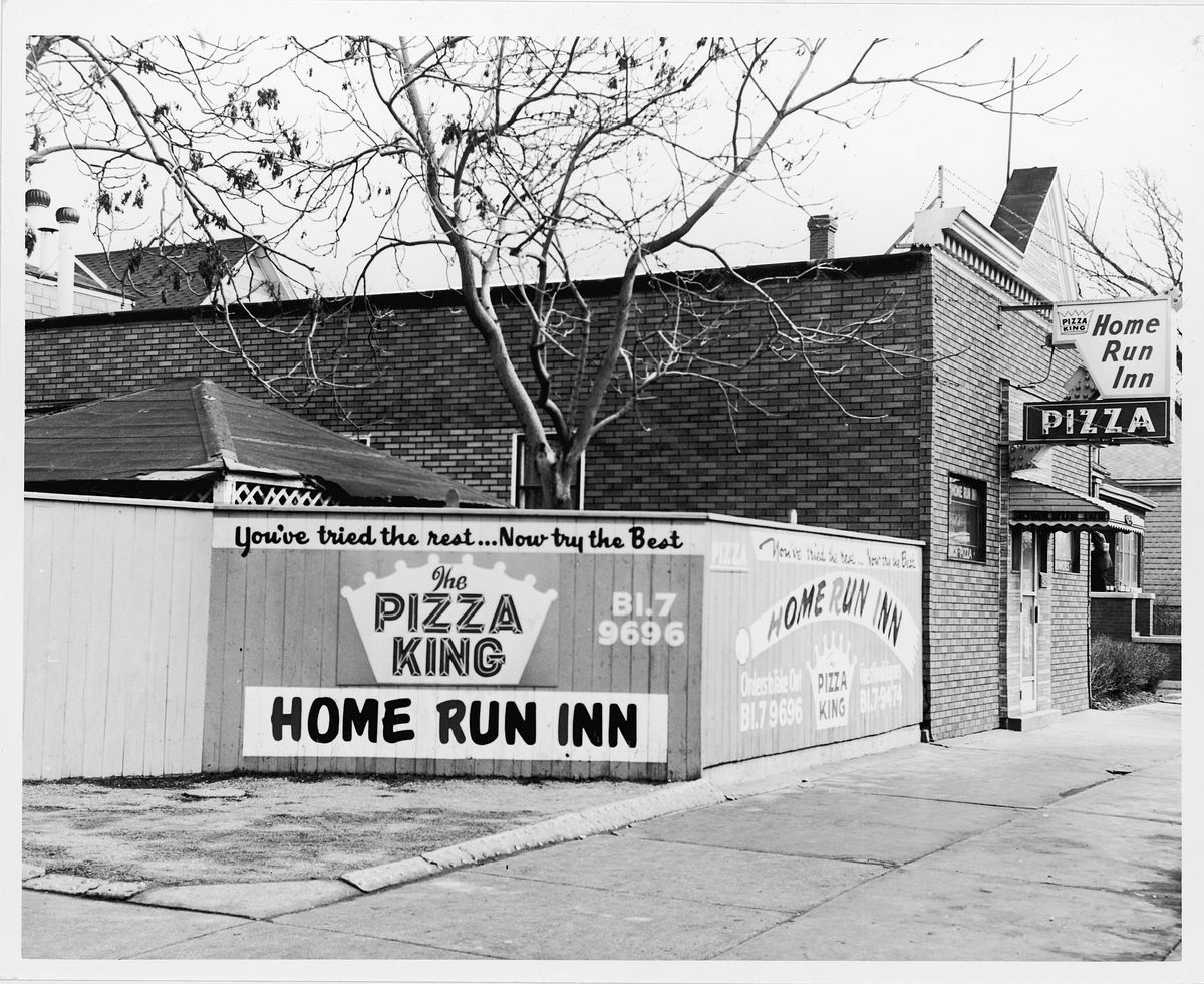 A black and white corner photo of an old pizzeria with fenced patio and old signs.