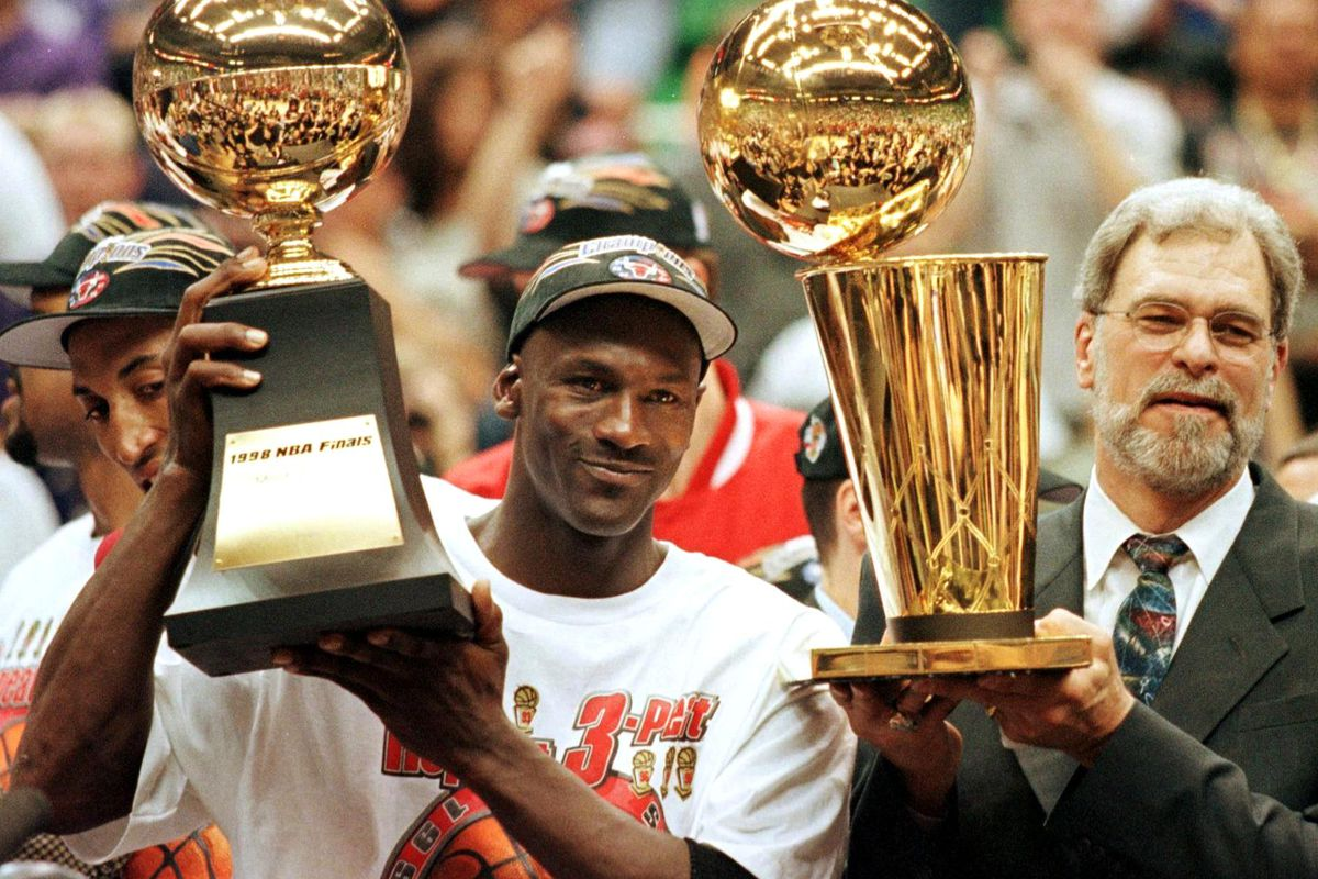 Michael Jordan and Phil Jackson celebrate a sixth NBA title after the Bulls beat the Jazz in Game 6 of the 1998 Finals.