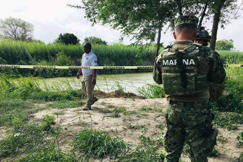 Mexican authorities walk along the Rio Grande bank where the bodies of Salvadoran migrant Oscar Alberto Martínez Ramírez and his nearly 2-year-old daughter Valeria were found, in Matamoros, Mexico, Monday, June 24, 2019, after they drowned trying to cross