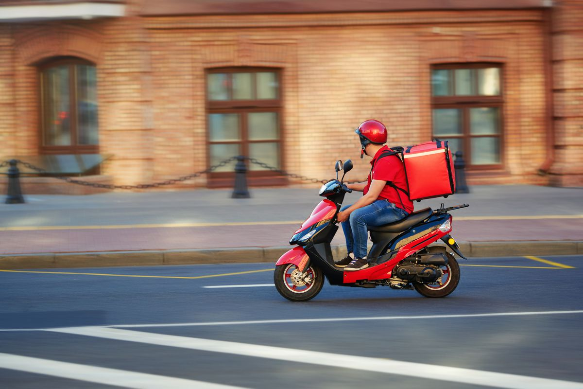 A biker in a red outfit bikes down an empty street with a red food delivery bag on his back