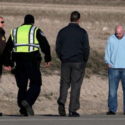 Law enforcement officers approach two bystanders at the scene where two bicyclists were hit by a pickup truck and died of their injuries in Lehi on Wednesday, March 12, 2014. Police said the cyclists were attempting to turn east near the intersection of Redwood Road and 2100 North just before 6 a.m. The driver of a pickup truck apparently did not see the pair and hit them.