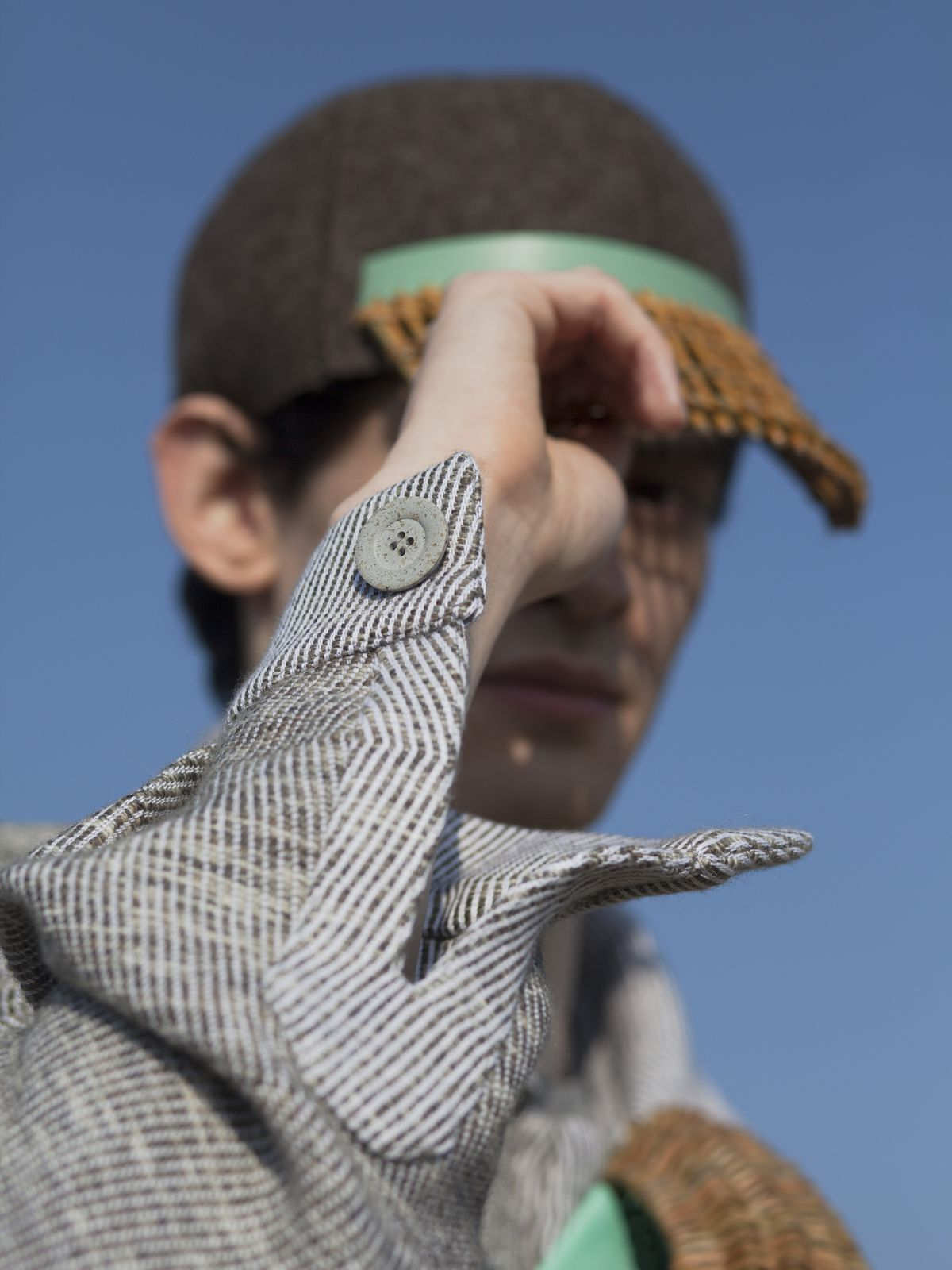 A detail of a man wearing a jacket tipping the brim of a ball cap made from rattan