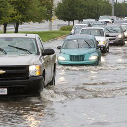 Traffic makes their way through a flooded portion of U.S. 52 after heavy rains from the remnants of Hurricane Isaac came through the area Saturday, September 1, 2012, in Lafayette, Ind.