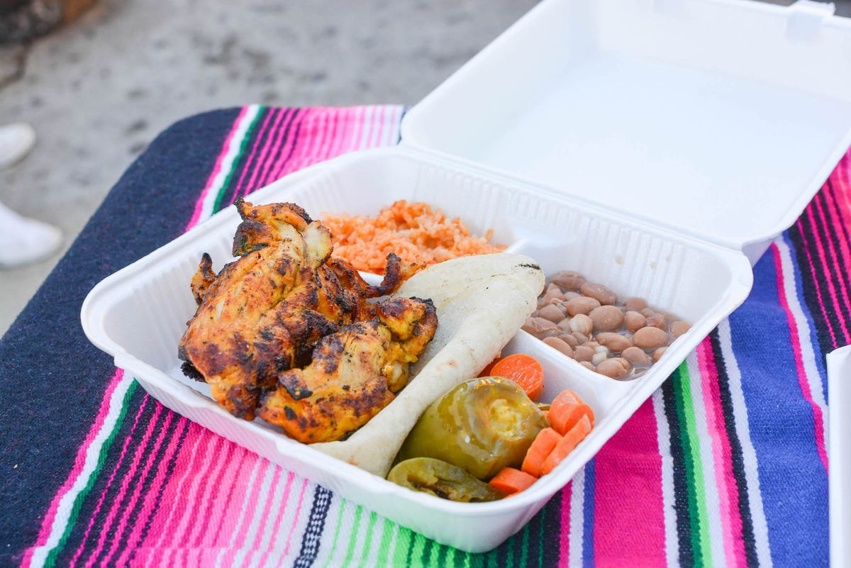 A Styrofoam plate with grilled chicken at a free food event.