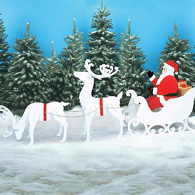 Santa, Sleigh, and Reindeer Wood Outdoor Christmas Decoration placed in a snowy backyard.