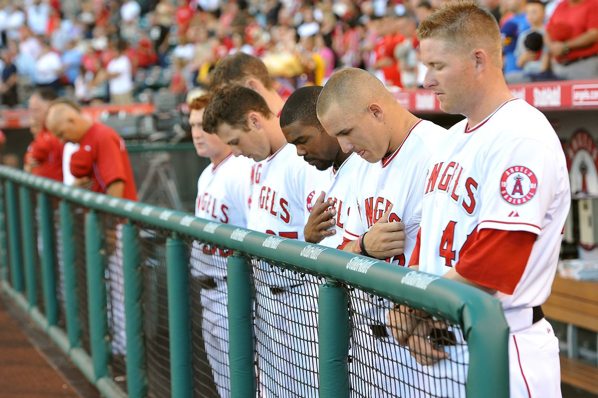Los Angeles Angels players bow their heads in a moment of silence for the shooting victims in Colorado before the game against the Texas Rangers at Angel Stadium.