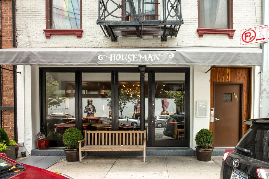 """A grey awning stretches out over a New York City sidewalk, with the word """"Houseman"""" in white"""