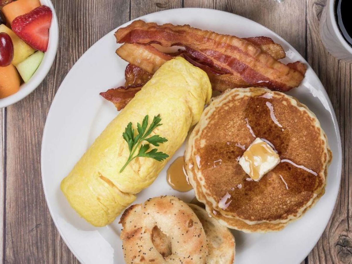 Fruit, an omelet, bacon, and pancakes on a white plate.