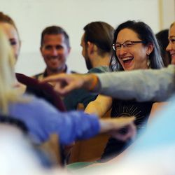 Meredith Peebles and others laugh as they follow promptings from Thomas McConkie of Lower Lights as he leads a group in mediation and discussion in Salt Lake City on Wednesday, June 14, 2017.