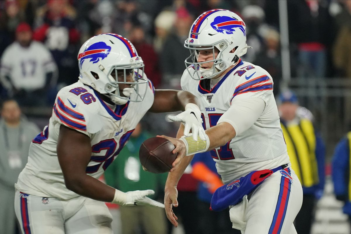Buffalo Bills quarterback Josh Allen hands off the ball to Buffalo Bills running back Devin Singletary as they take on the New England Patriots in the second quarter at Gillette Stadium.