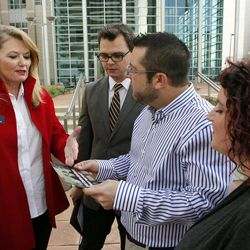 State Senator Jean White, left, shows Brian Edwards, Tom Privitere and photographer Kristina Hill, right, a brochure with an altered photograph that she took of Tom Privitere and his partner Brian Edwards outside the federal courthouse in Denver on Wednesday, Sept. 26, 2012. Privitere, Edwards and Hill filed a lawsuit in federal court on Wednesday over the fact that the photo was altered and used in a political campaign in Colorado.