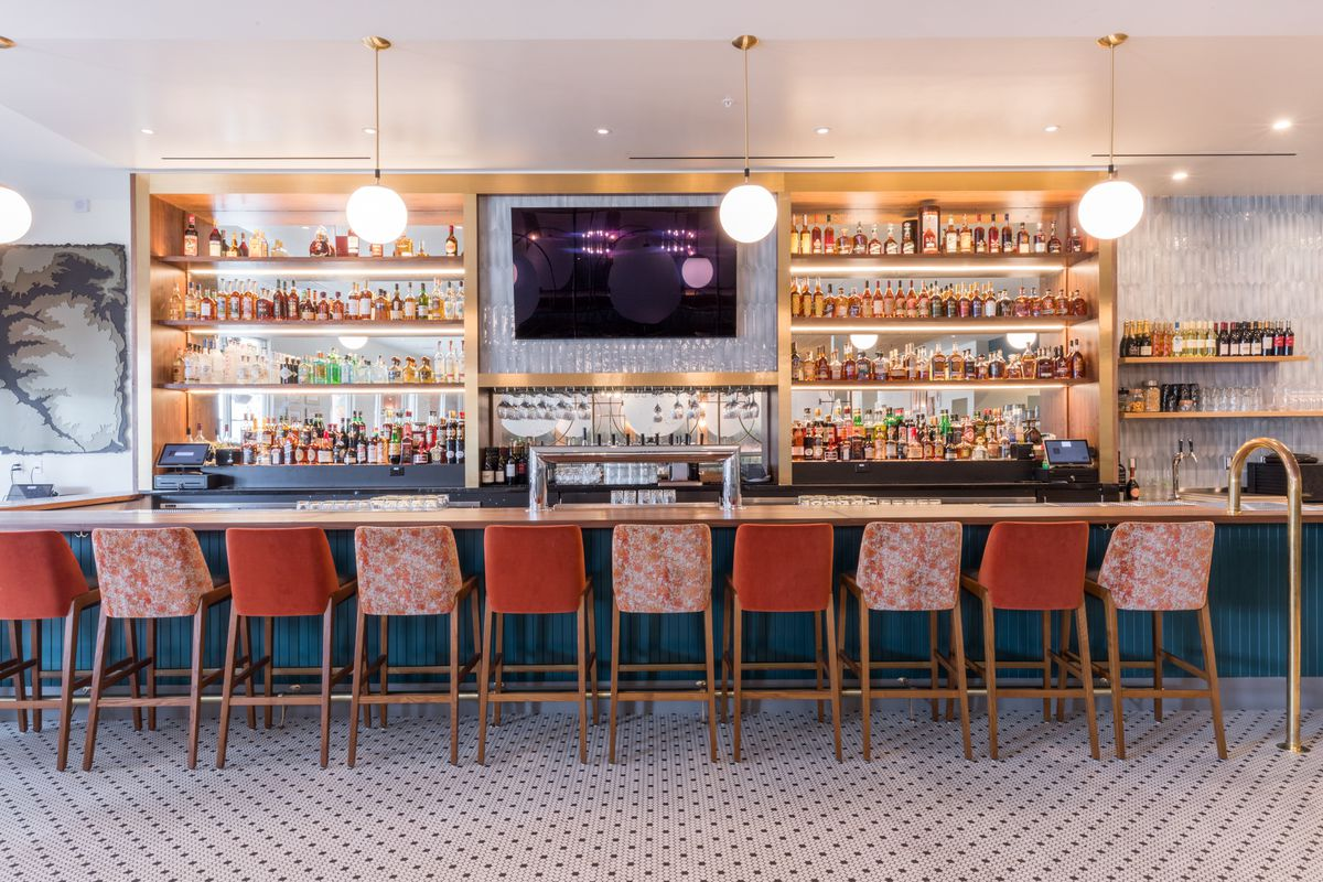 The Parisian bistro-style bar has orange stools with brass legs, gold accents, and white-and-black tiled floors.