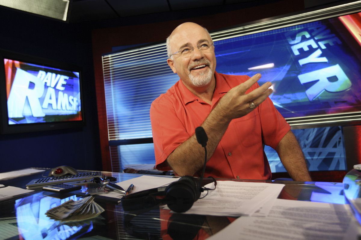 Dave Ramsey, a conservative media figure and financial expert, smiles sitting at a desk in his broadcasting studio.