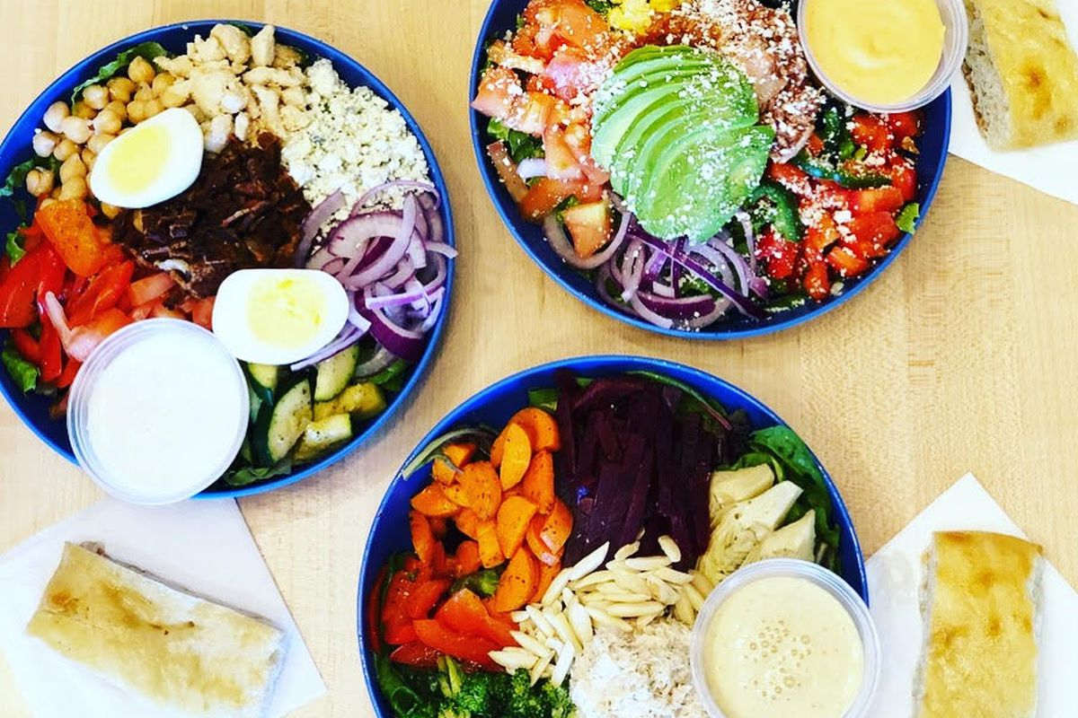 A bird's eye view of three salads with various vegetables, such as avocado, corn, broccoli, and red peppers.