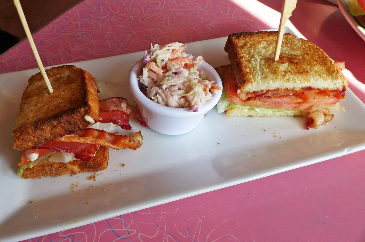 Two halves of a BLT with toothpicks holding them together sit on a rectangular place with coleslaw in between.