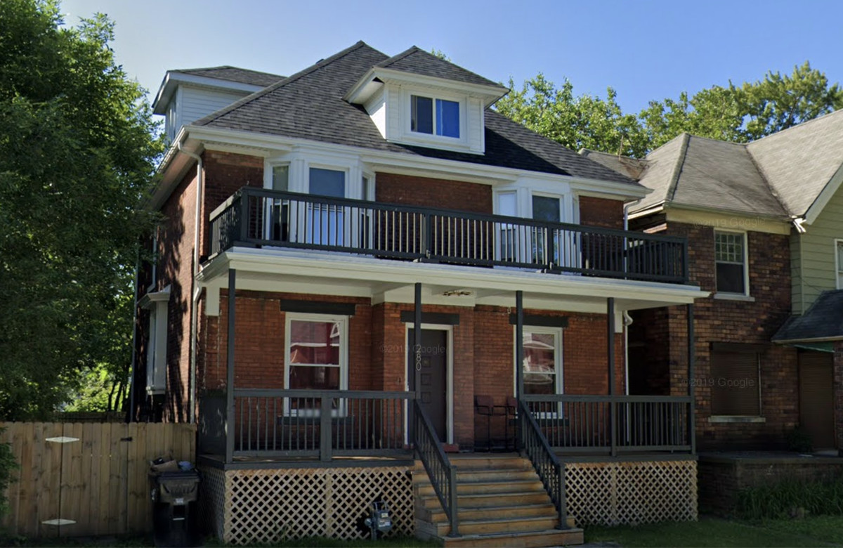 A two story brick house with a front porch and deck.