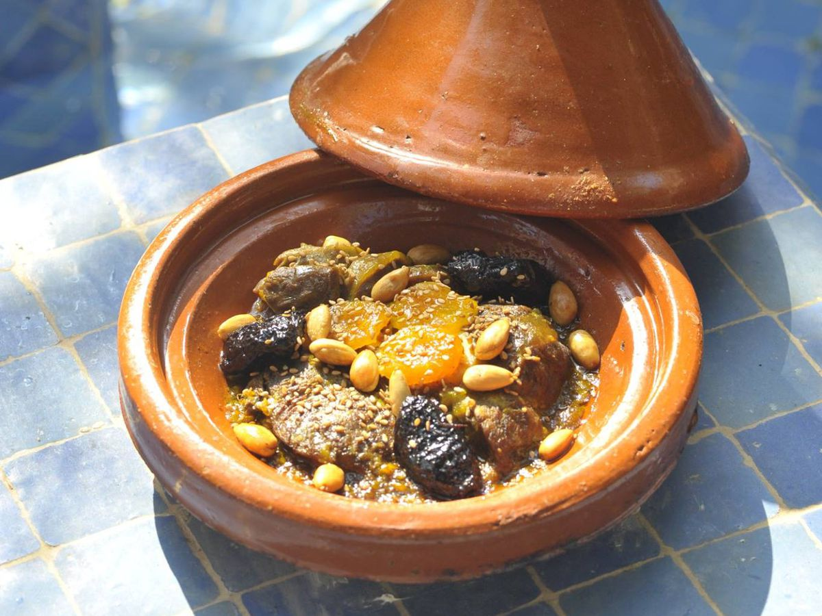 A tagine, sitting on a tiled pedestal, with the lid opened to show a meal inside