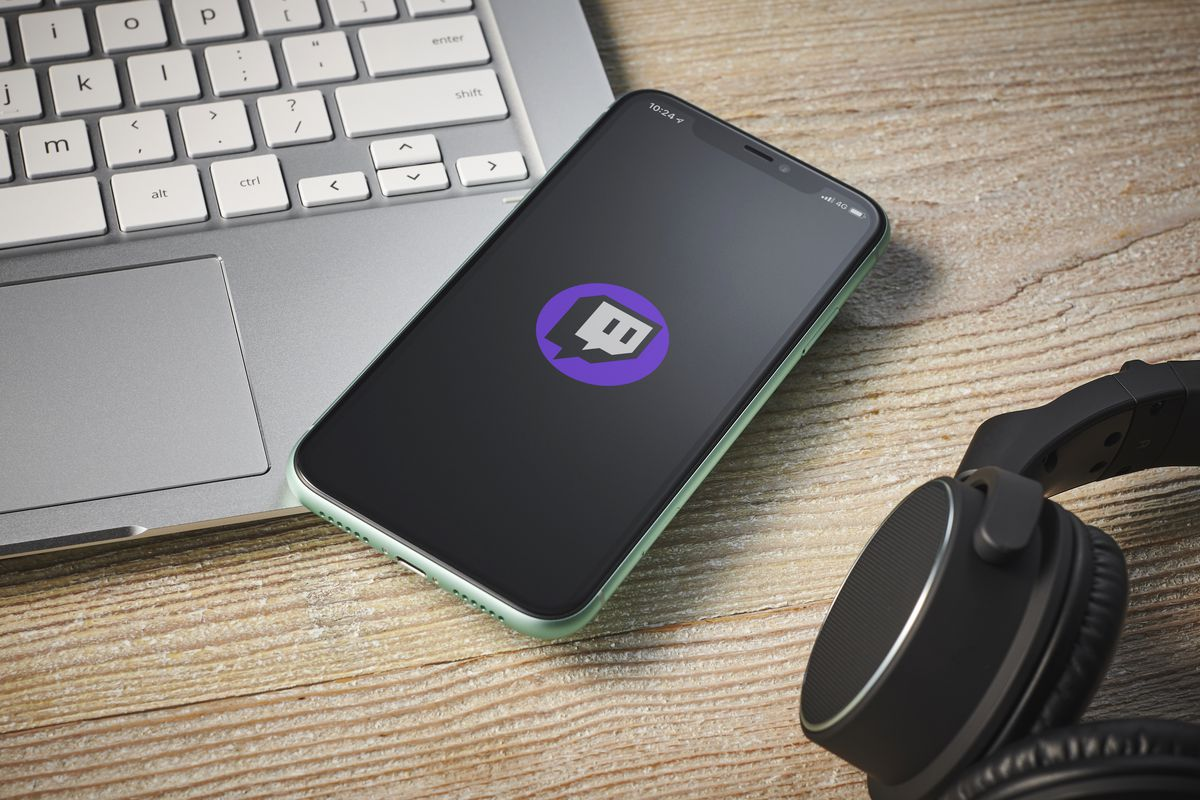 An open laptop, a cellphone displaying the Twitch icon, and a set of over-ear headphones all sitting on a table top.