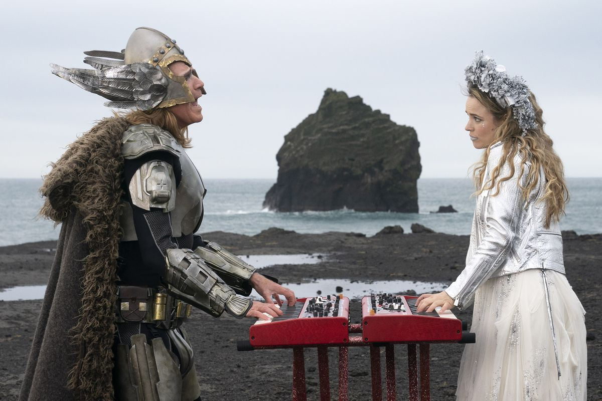 A man and a woman in Viking-style costumes stand with keyboards between them in an Icelandic landscape.
