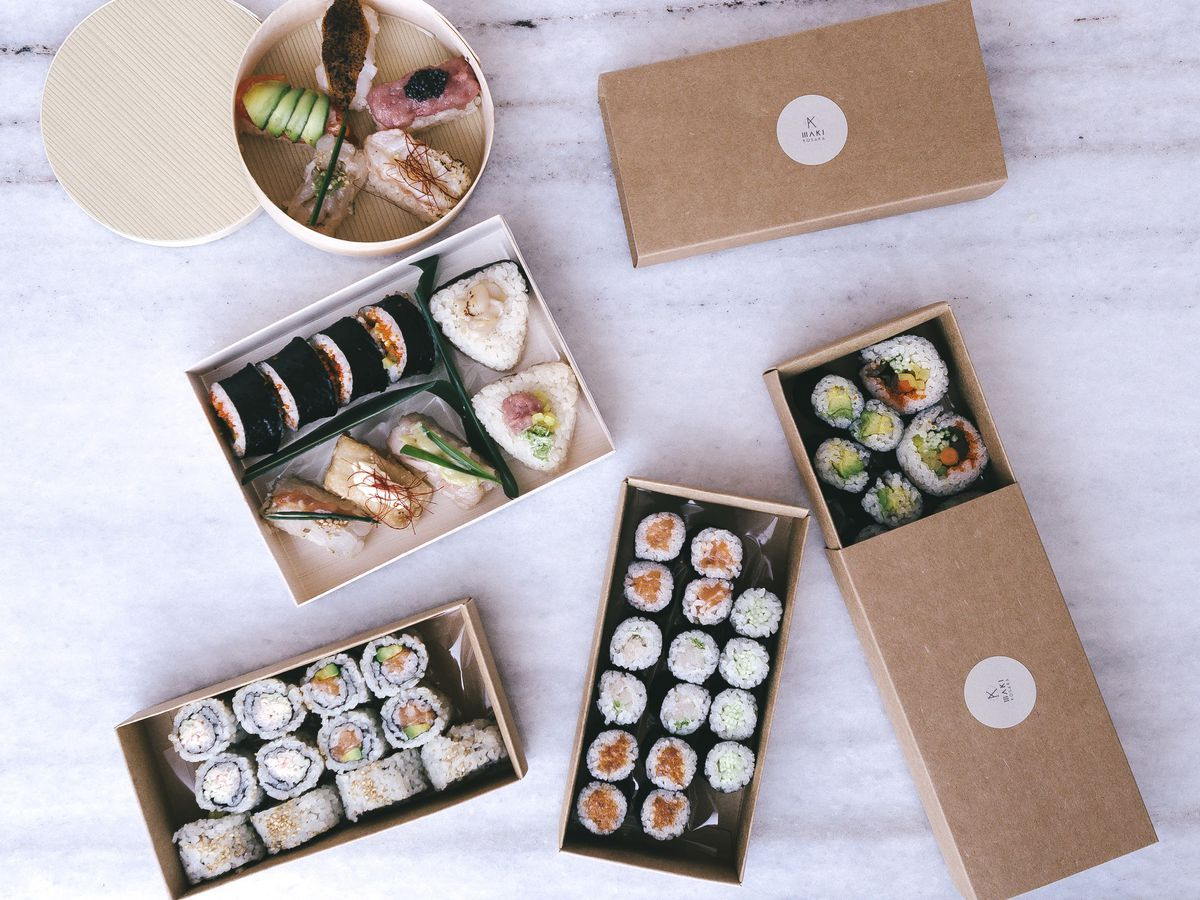 Boxes of sushi laid out on a white marble table